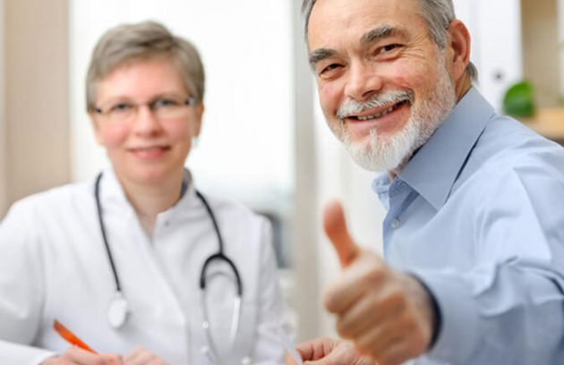 a patient giving thumbs up with doctor in the background
